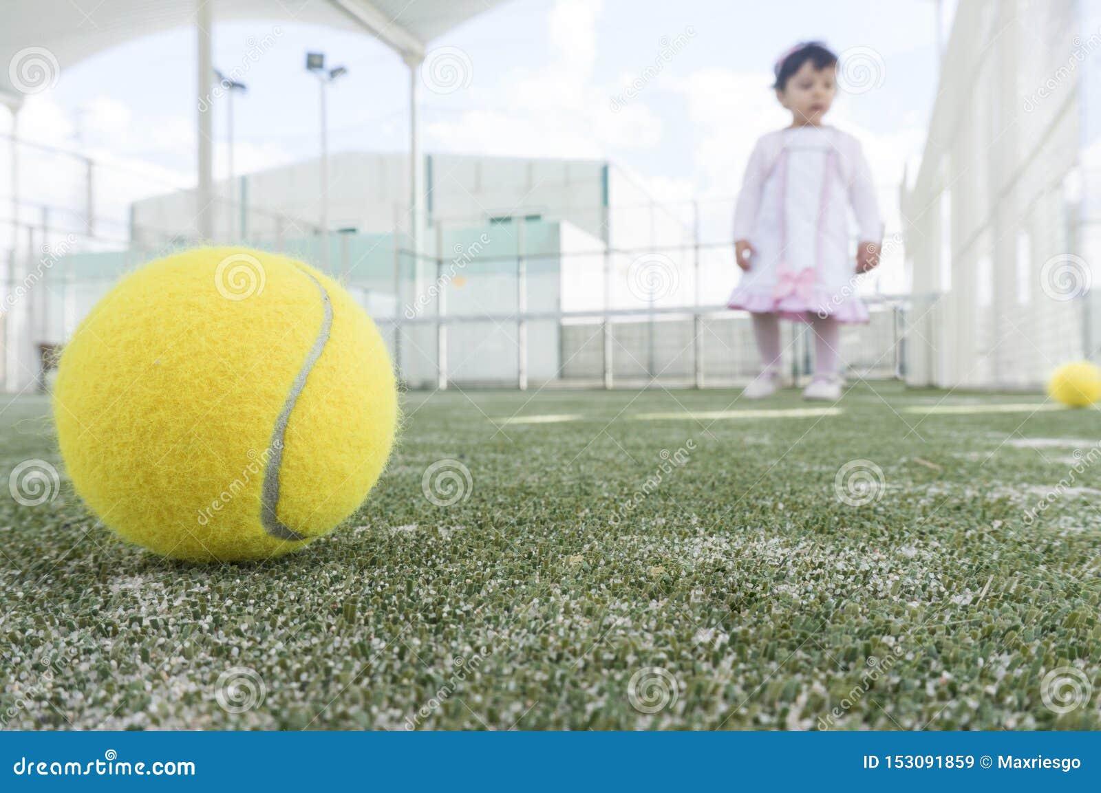 Bebé en la pista de tenis de la paleta que aprende cómo jugar