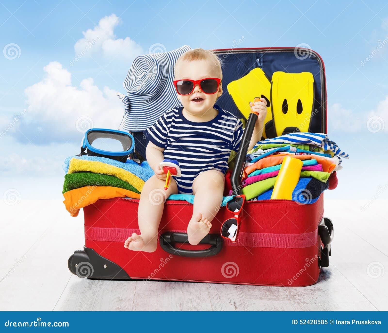 Bebé en maleta del viaje Niño dentro del equipaje lleno para las vacaciones