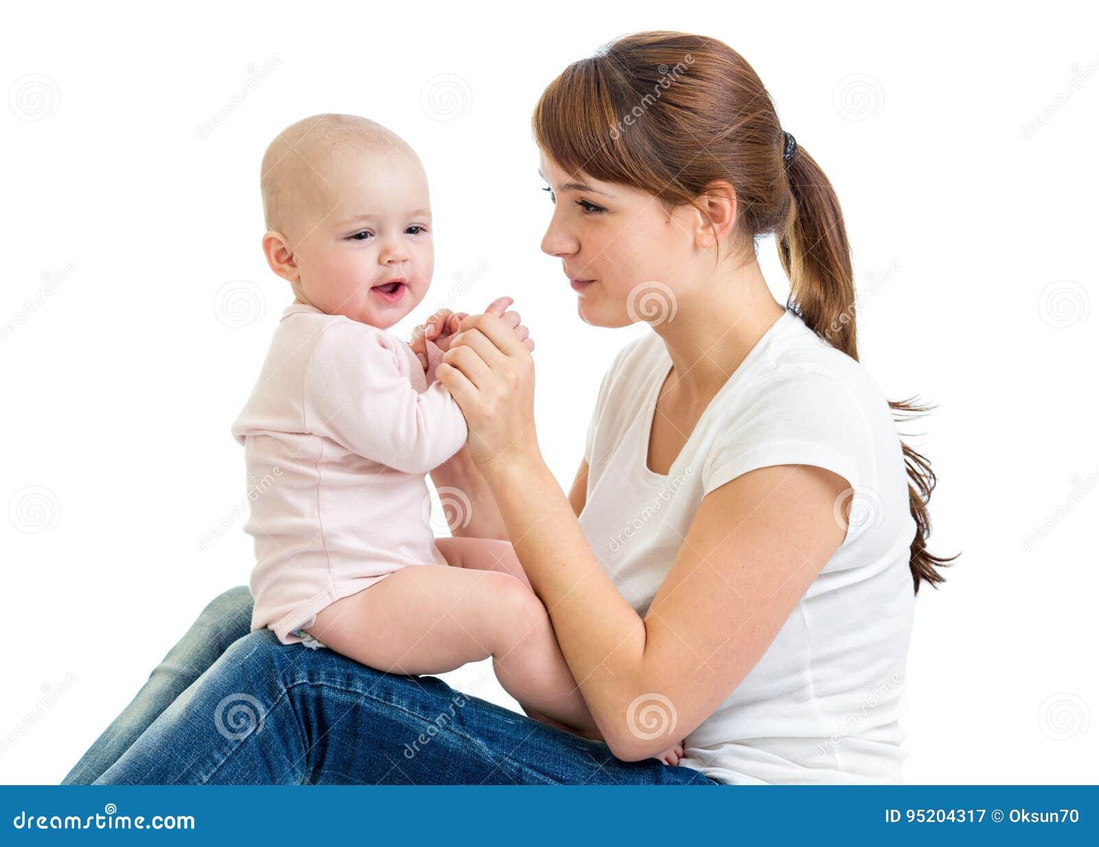 Bebé encantador que parece ausente y que sonríe mientras que se sienta en sus rodillas del ` s de la madre La mamá está mirando a
