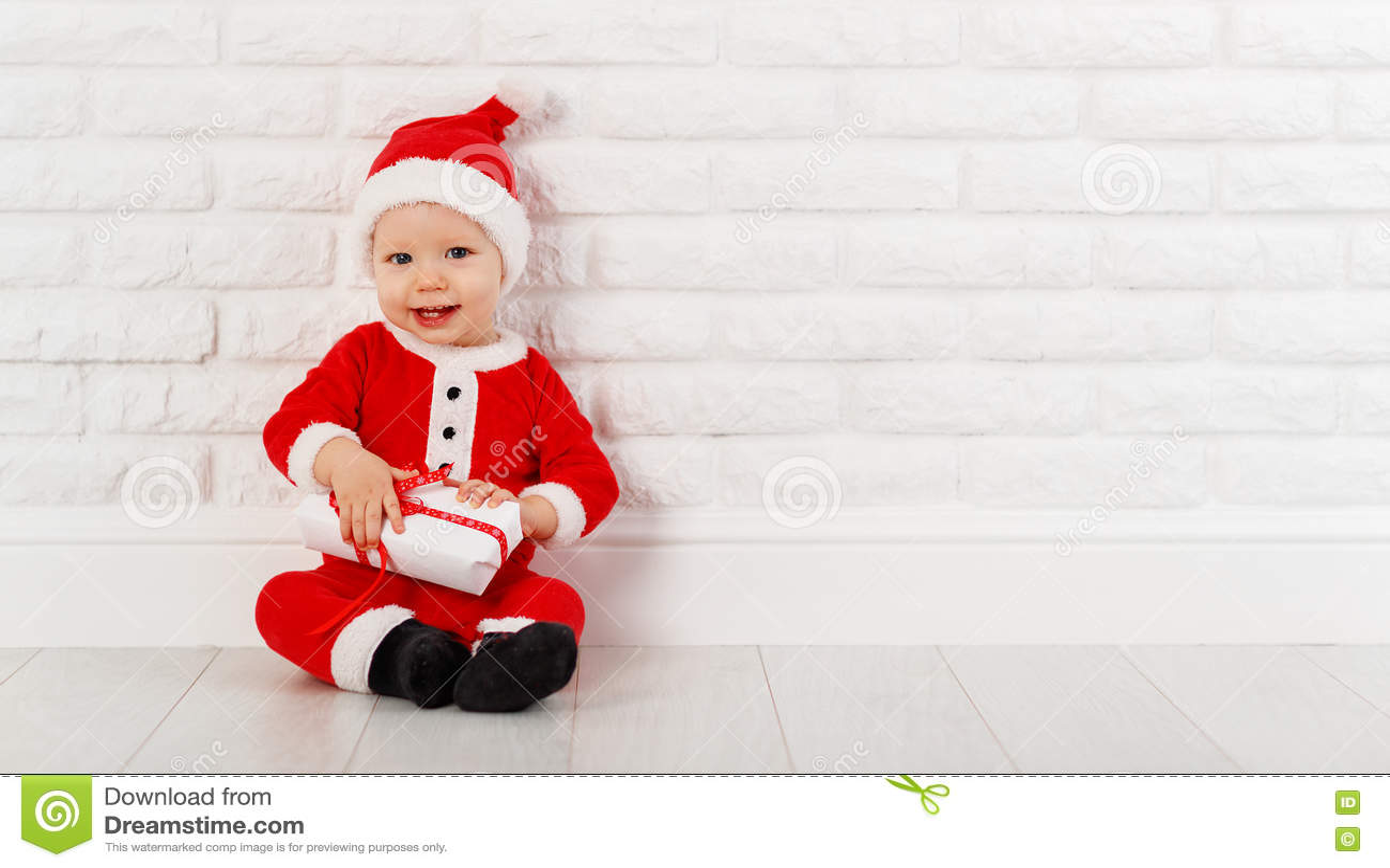 Bebé feliz en un traje Santa Claus de la Navidad con los regalos
