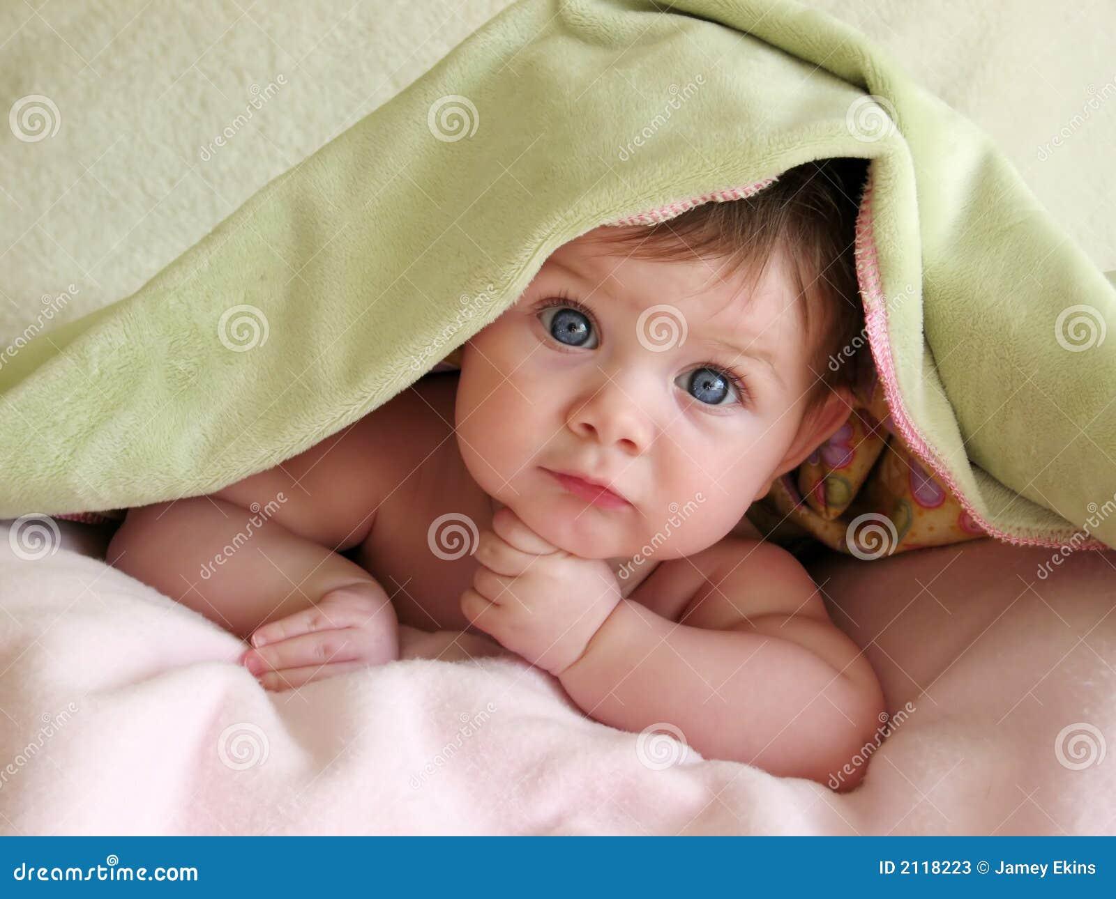 Bebé hermoso bajo la manta