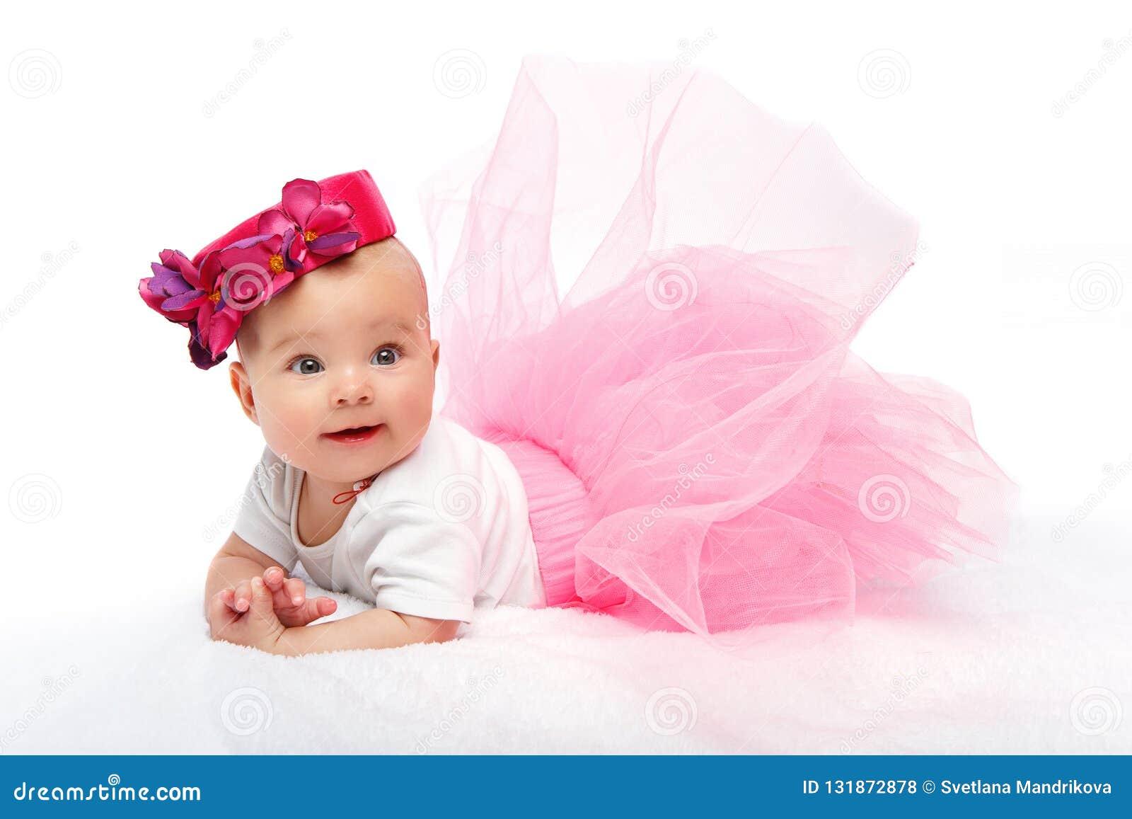 Bebé hermoso feliz con el sombrero rosado en la cabeza