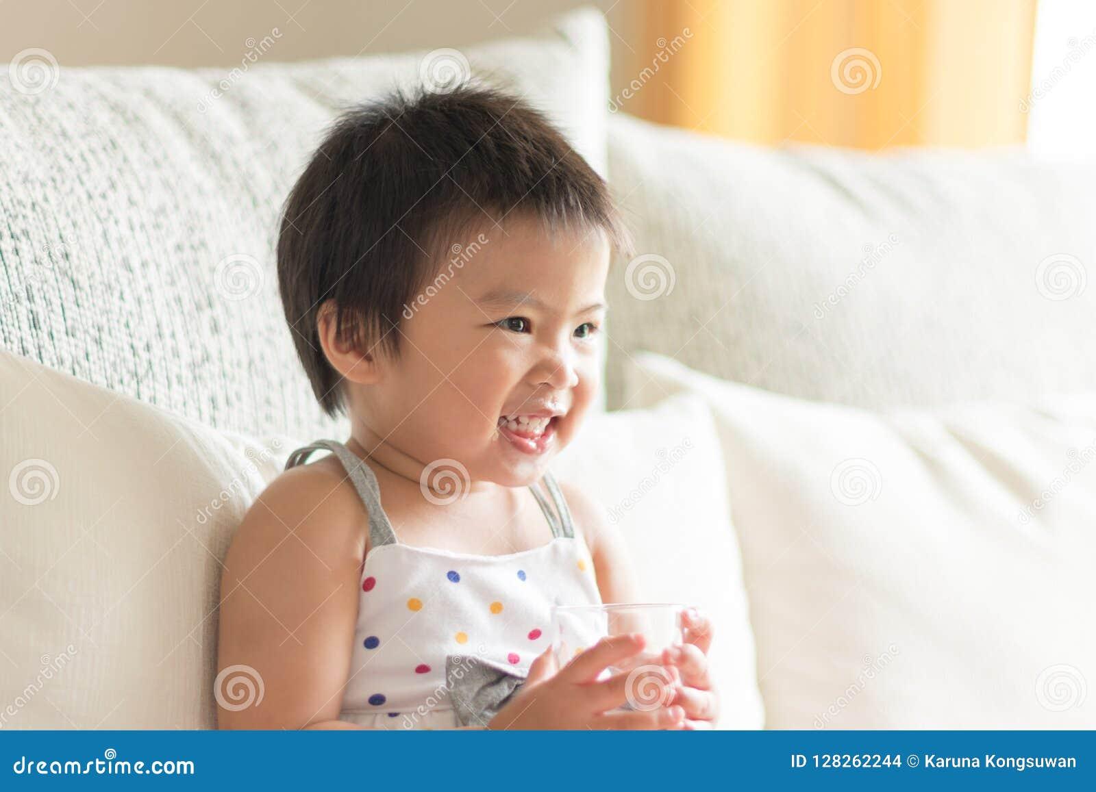 Bebé lindo asiático que sonríe y que sostiene un vidrio de agua Conce
