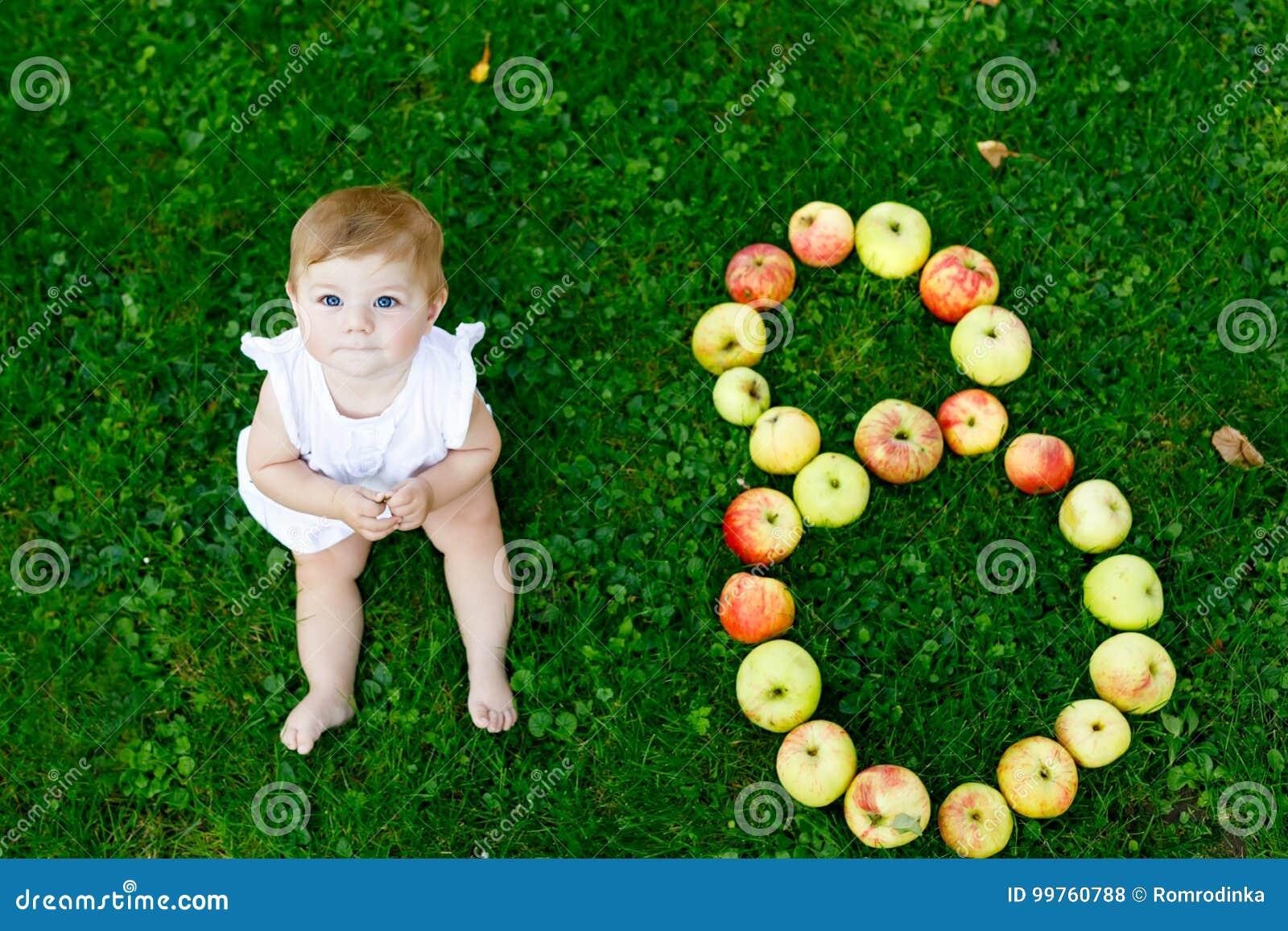 Bebé lindo con el número 8 como ocho meses hechos con las manzanas maduras