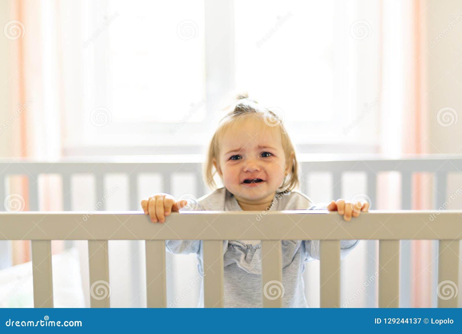 Bebé lindo del bebé en el pesebre del sitio del bebé