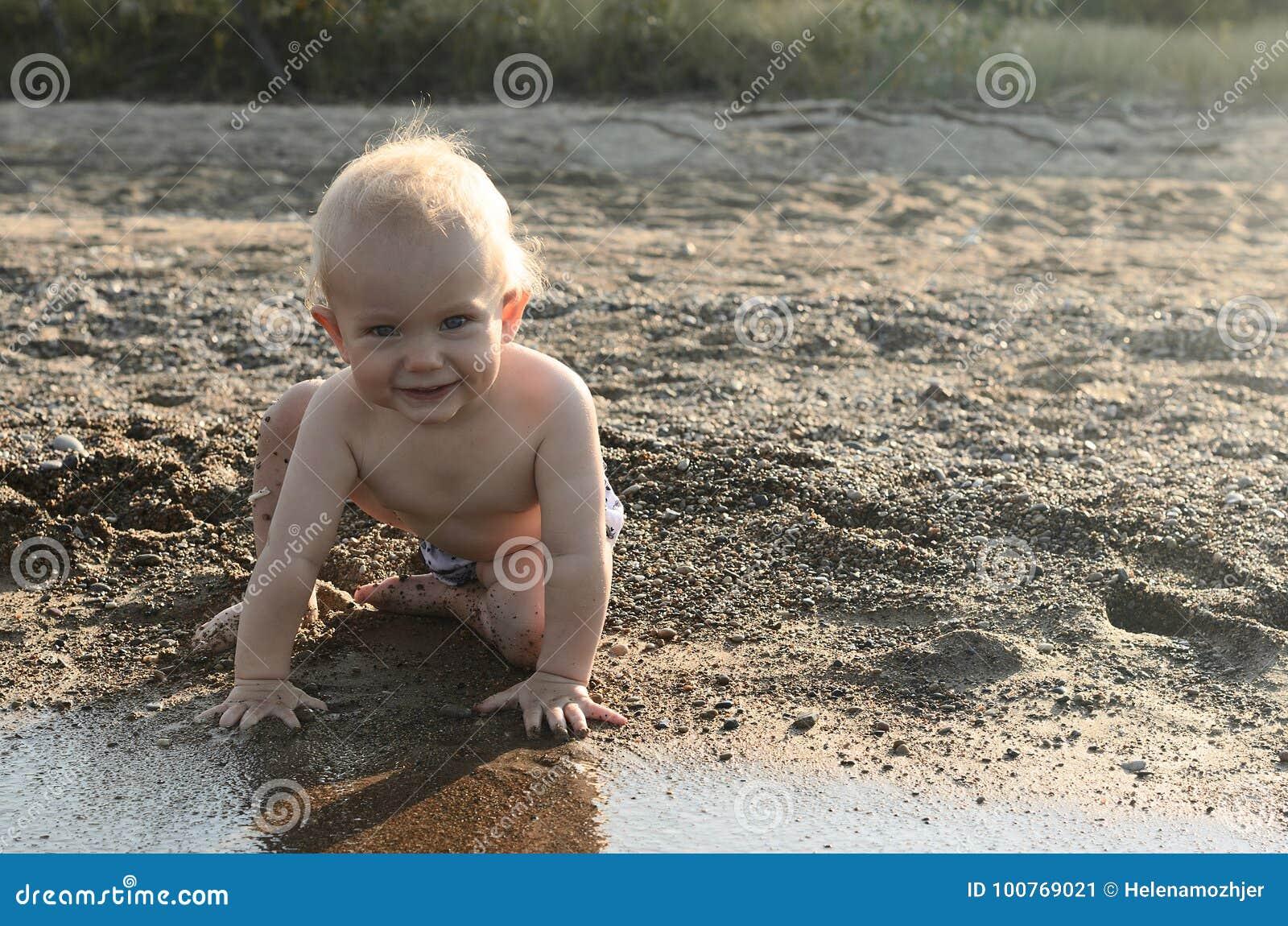 Bebé lindo en la playa que sonríe y que mira la cámara Outdoo