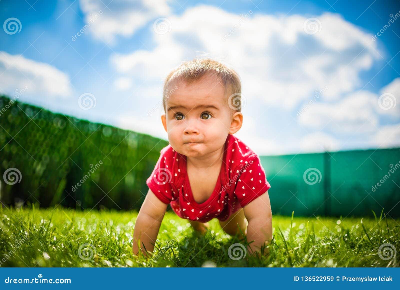 Bebé lindo en todos los fours en cuerpo rojo en hierba verde con el cielo azul y las nubes