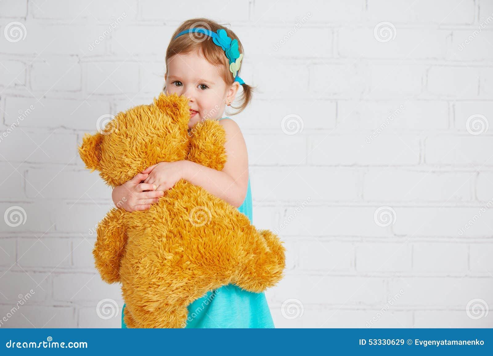 Bebé que abraza un oso de peluche amado