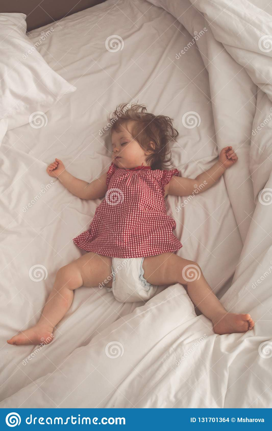 Bebé que duerme en la parte posterior con los brazos abiertos y sin el pacificador en una cama con las hojas blancas El dormir pa