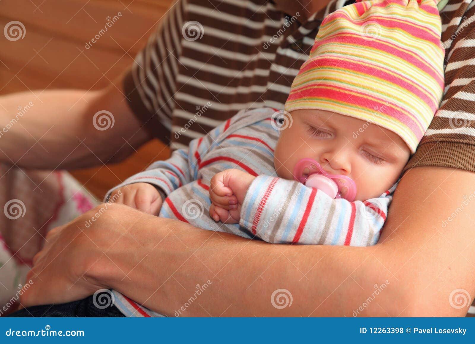 Bebé que duerme en las manos del hombre