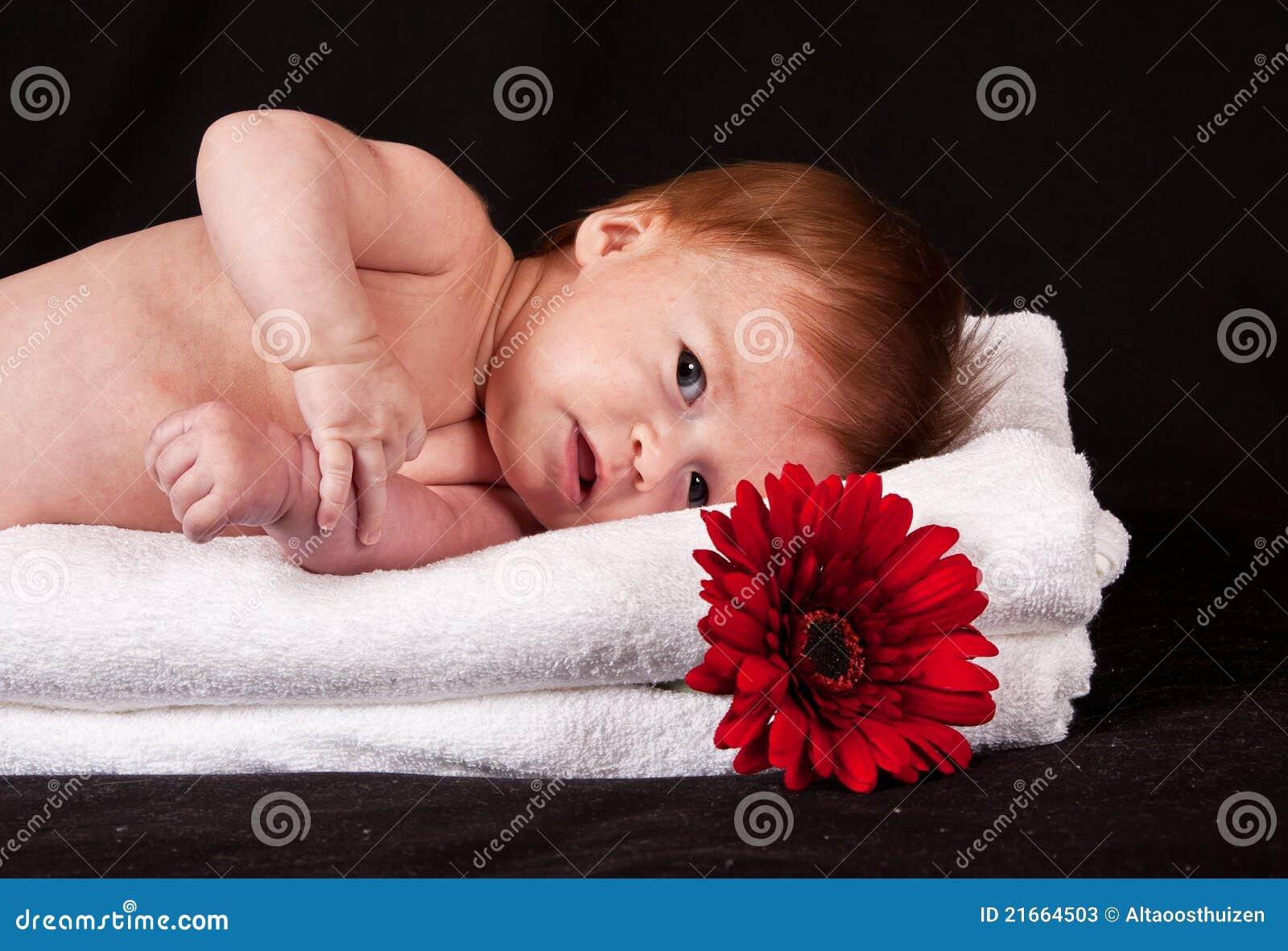Bebé que encontra-se nas toalhas brancas