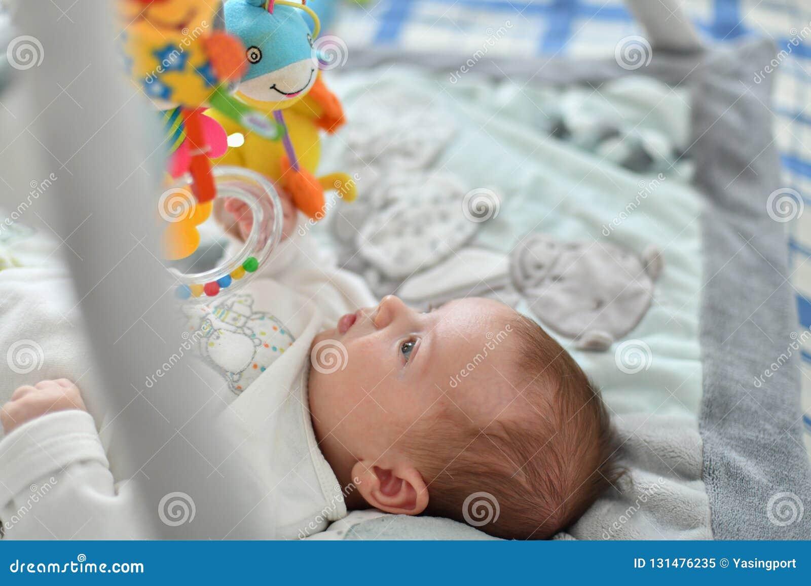 Bebé que juega con los juguetes de la ejecución en la estera que se convierte