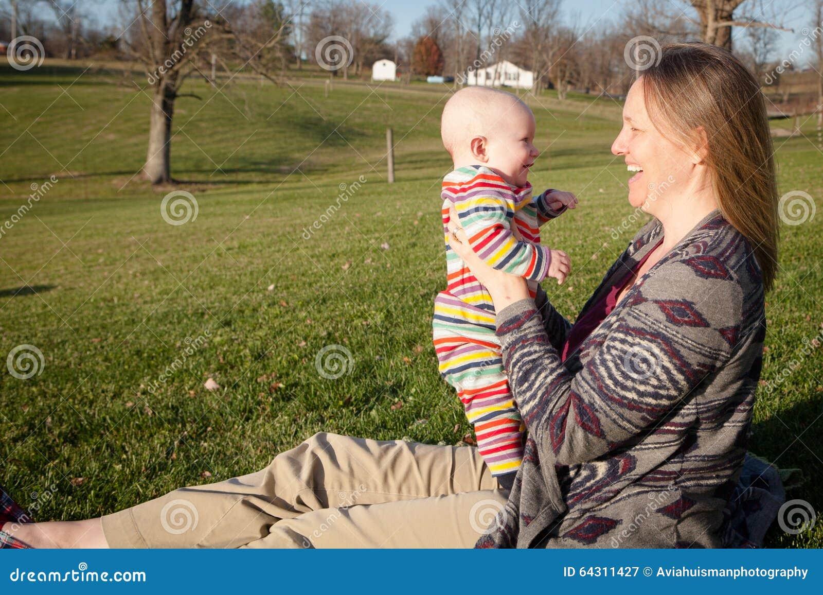 Bebé que ríe con la mamá afuera