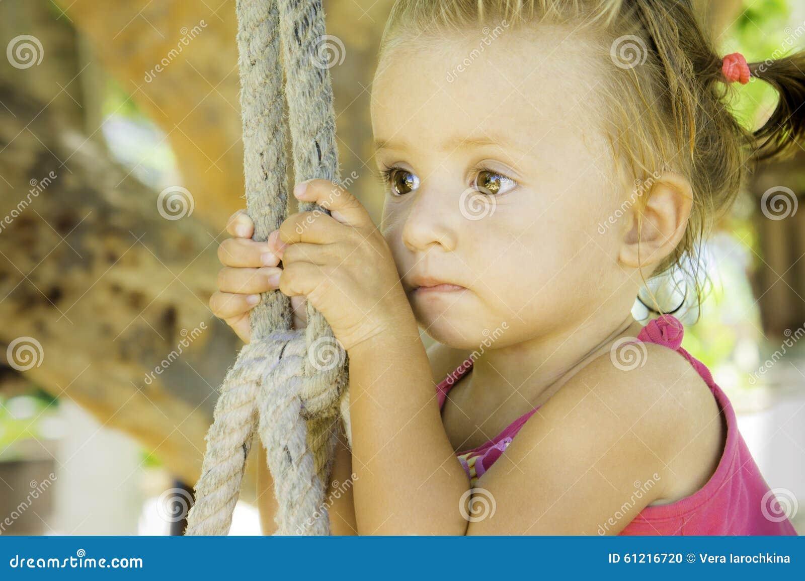 Bebé que se sienta en el oscilación y que mira apagado en la distancia ella tiene ojos muy hermosos