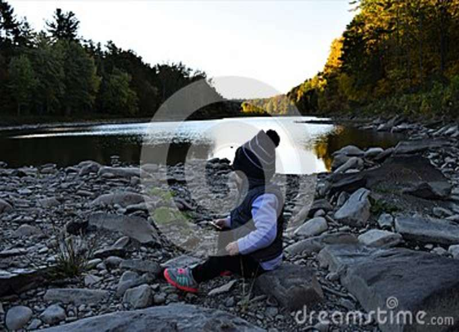 Bebé que se sienta en el río