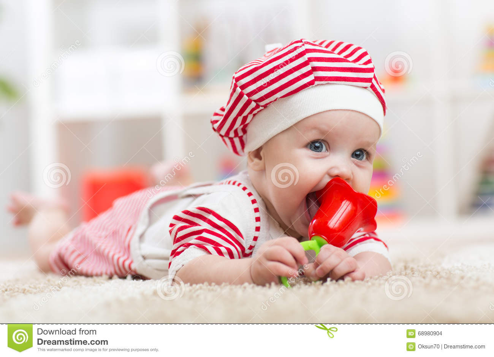 Bebé que sostiene un juguete y que miente en el vientre en el cuarto de niños