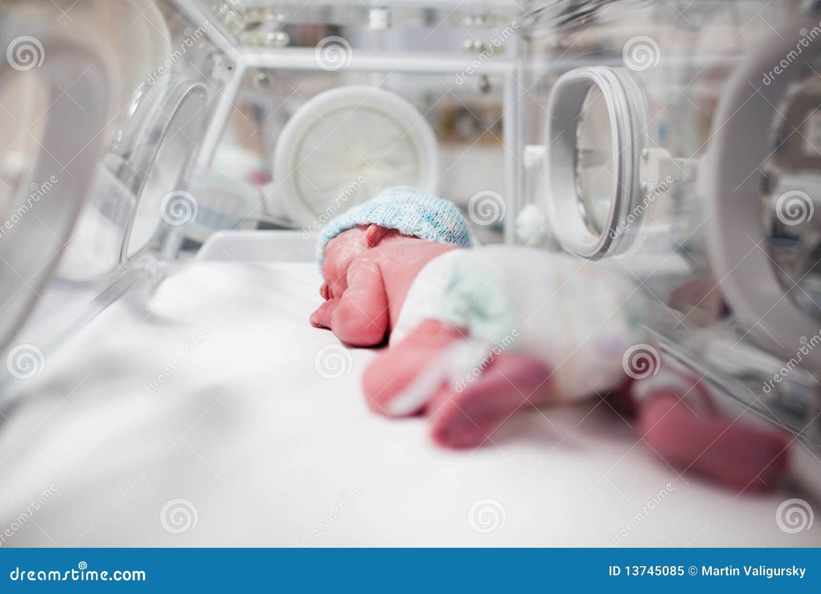Bebé recém-nascido coberto no vertix na incubadora
