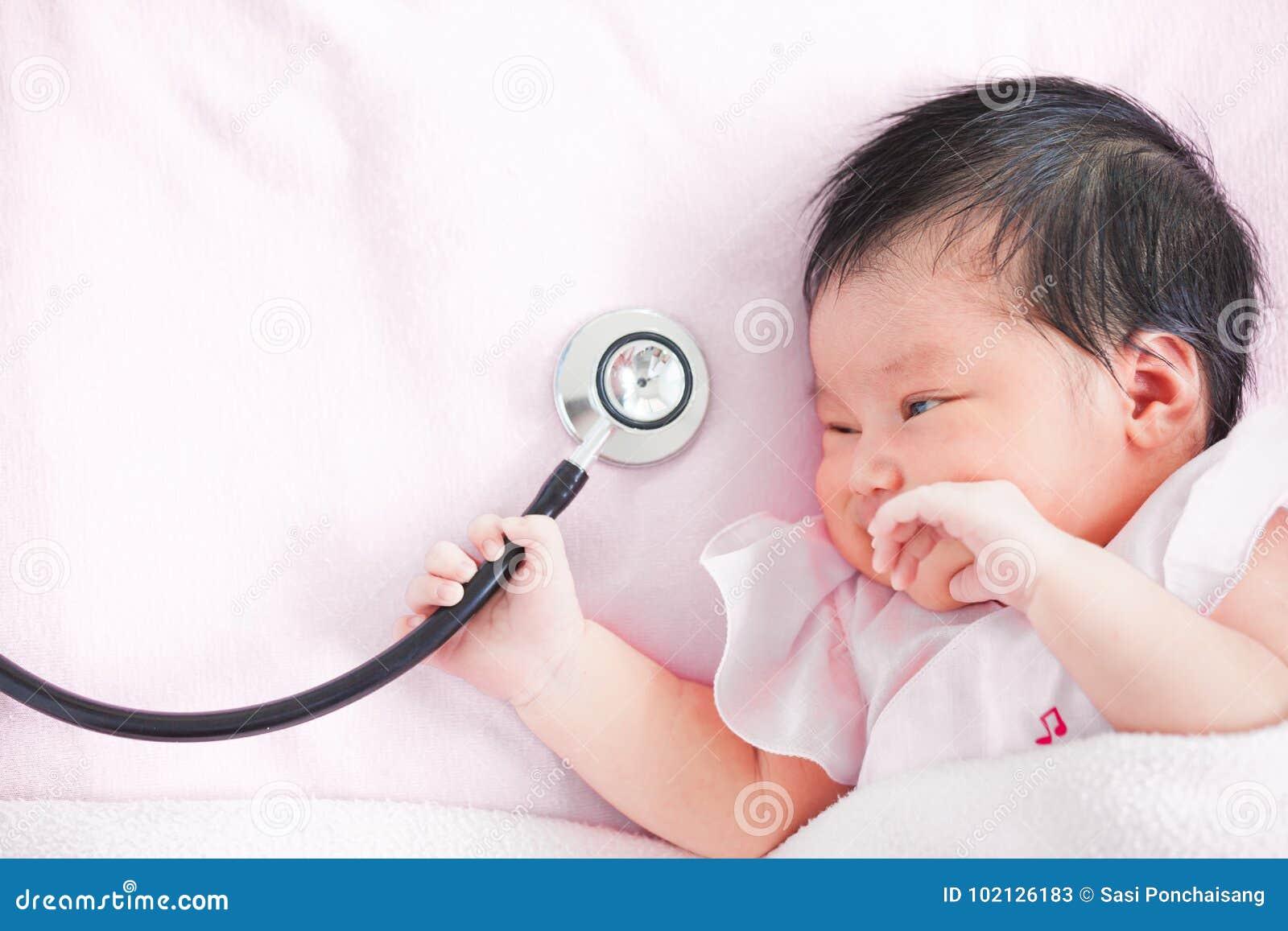 Bebé recién nacido asiático lindo que sonríe y que sostiene el estetoscopio