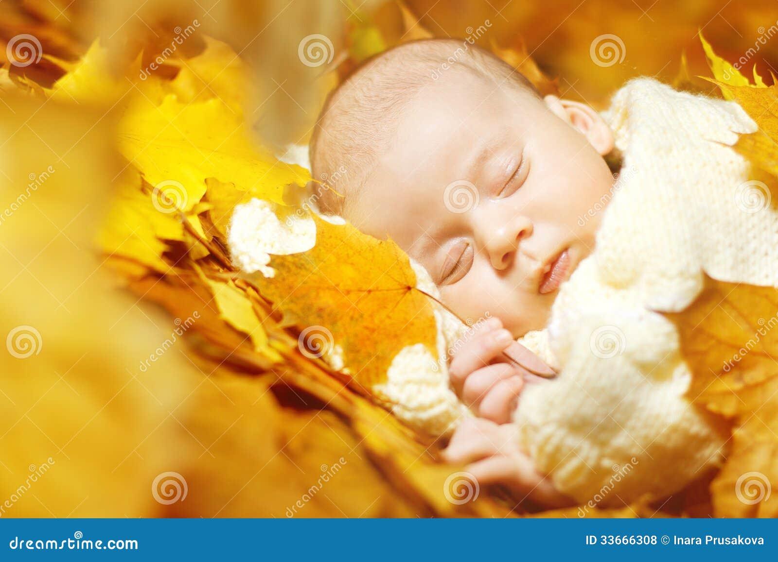 Bebé recién nacido del otoño que duerme en hojas amarillas