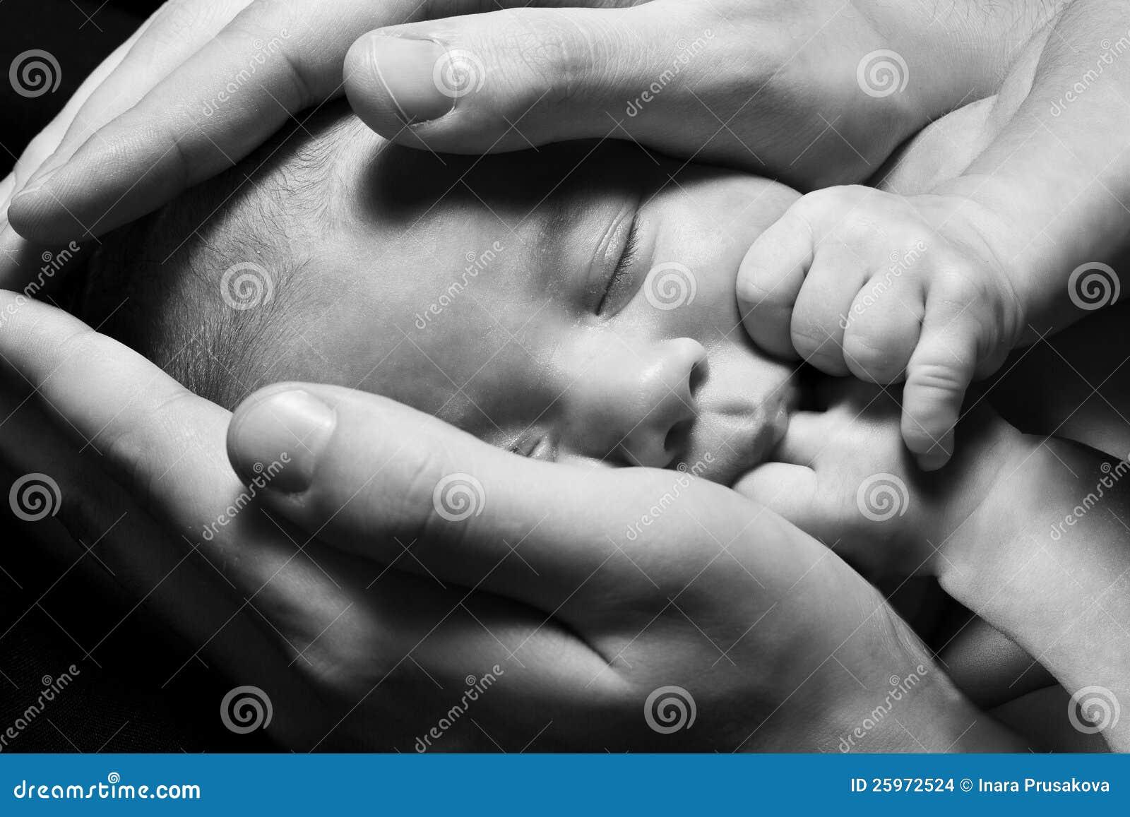 Bebé recién nacido que duerme en las manos de los padres. Concepto.