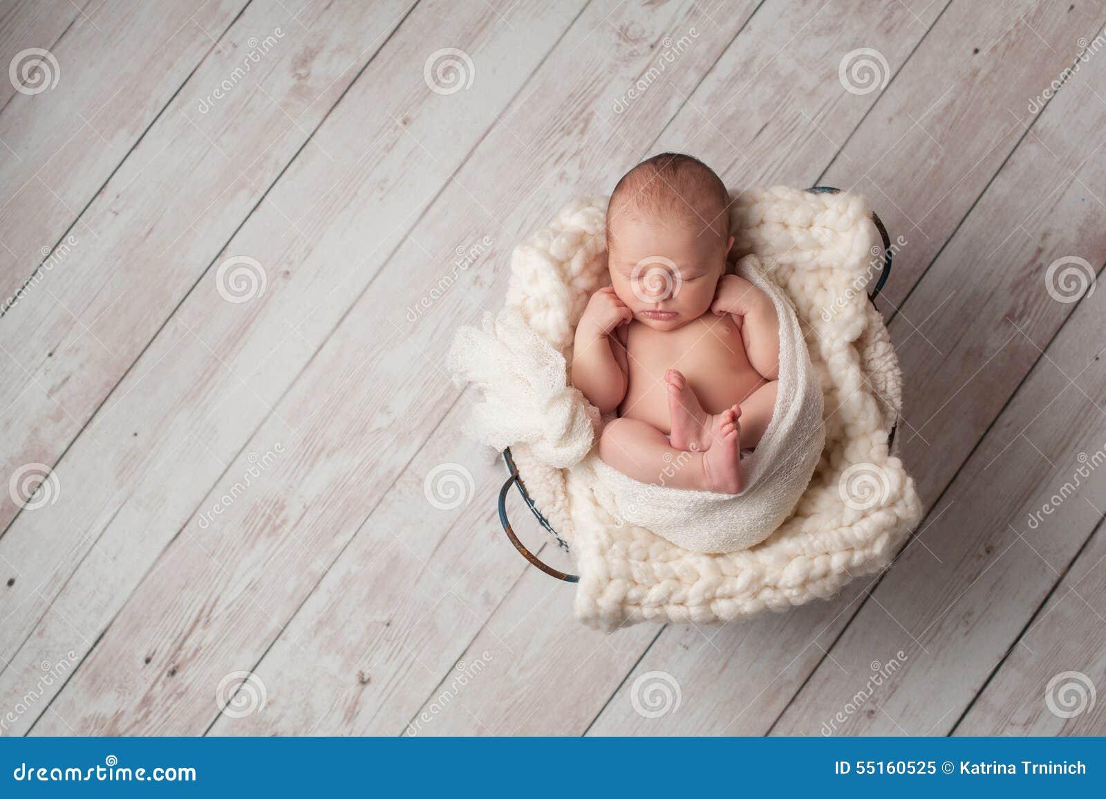 Bebé recién nacido que duerme en una cesta de alambre