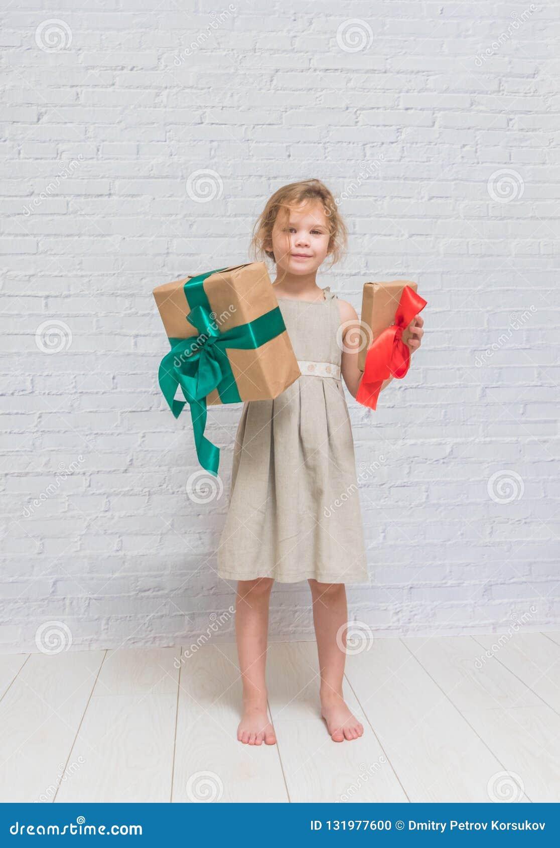 Bebé, regalo de cumpleaños de la muchacha, día de fiesta, la Navidad, pared de ladrillo blanca b