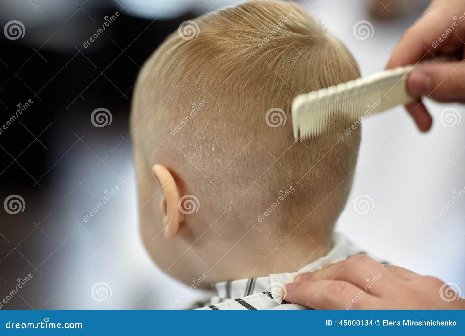 Beb? rubio lindo en una peluquer?a de caballeros que tiene corte de pelo del peluquero Manos del estilista con el cepillo para el