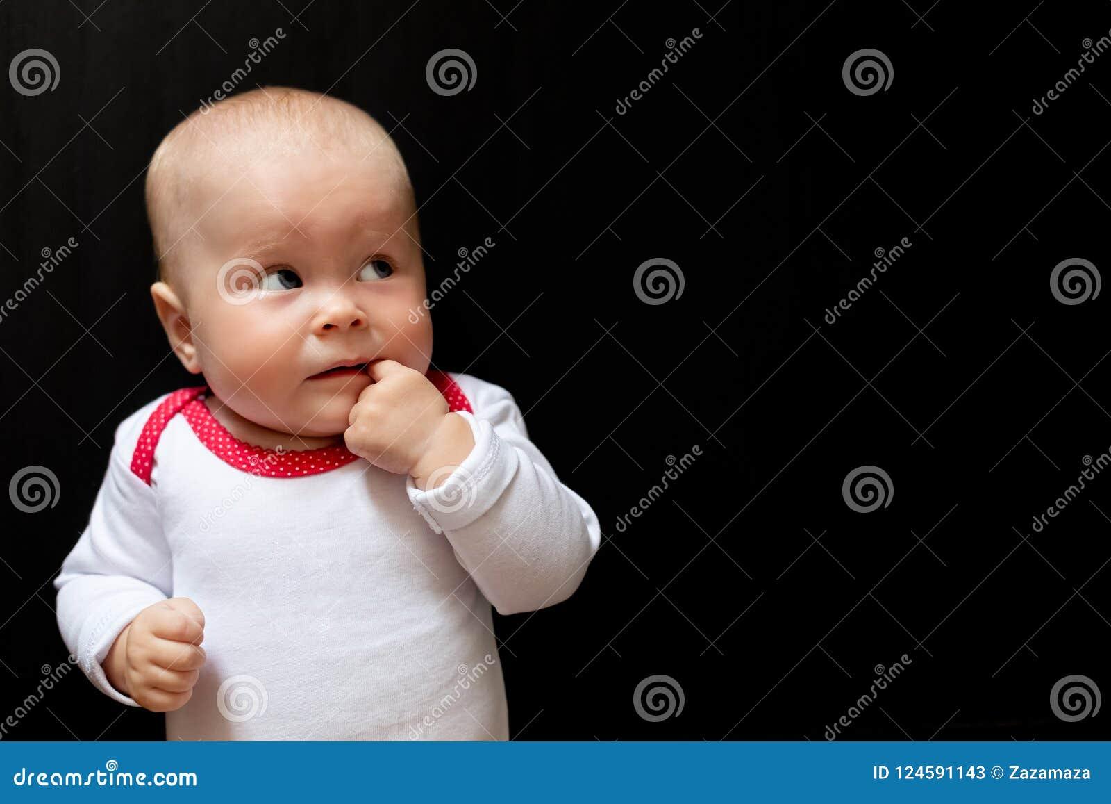 Bebê adorável e bonito com olhos azuis e com seu dedo na boca e na vista acima Infante no preto