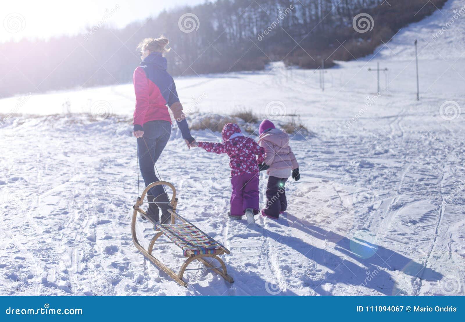 Bebê adorável em uma neve branca na situação morna do terno na neve