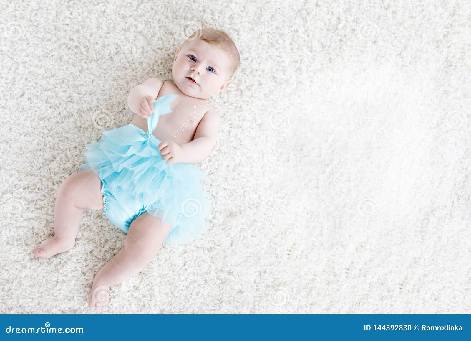 Bebê adorável na saia vestindo do tutu de turquesa do fundo branco Criança pequena bonito que ri e que sorri feliz