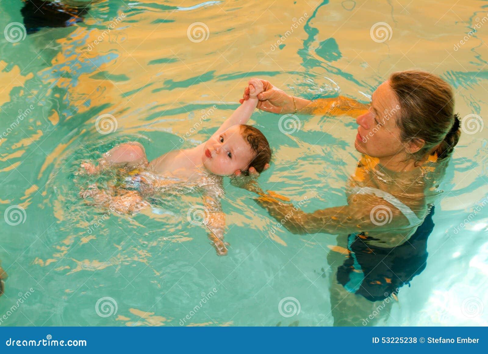 Bebê adorável que aprecia nadar em uma associação com sua mãe