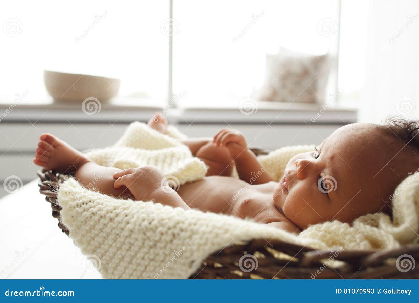 Bebê adorável que encontra-se no berço de vime pela janela