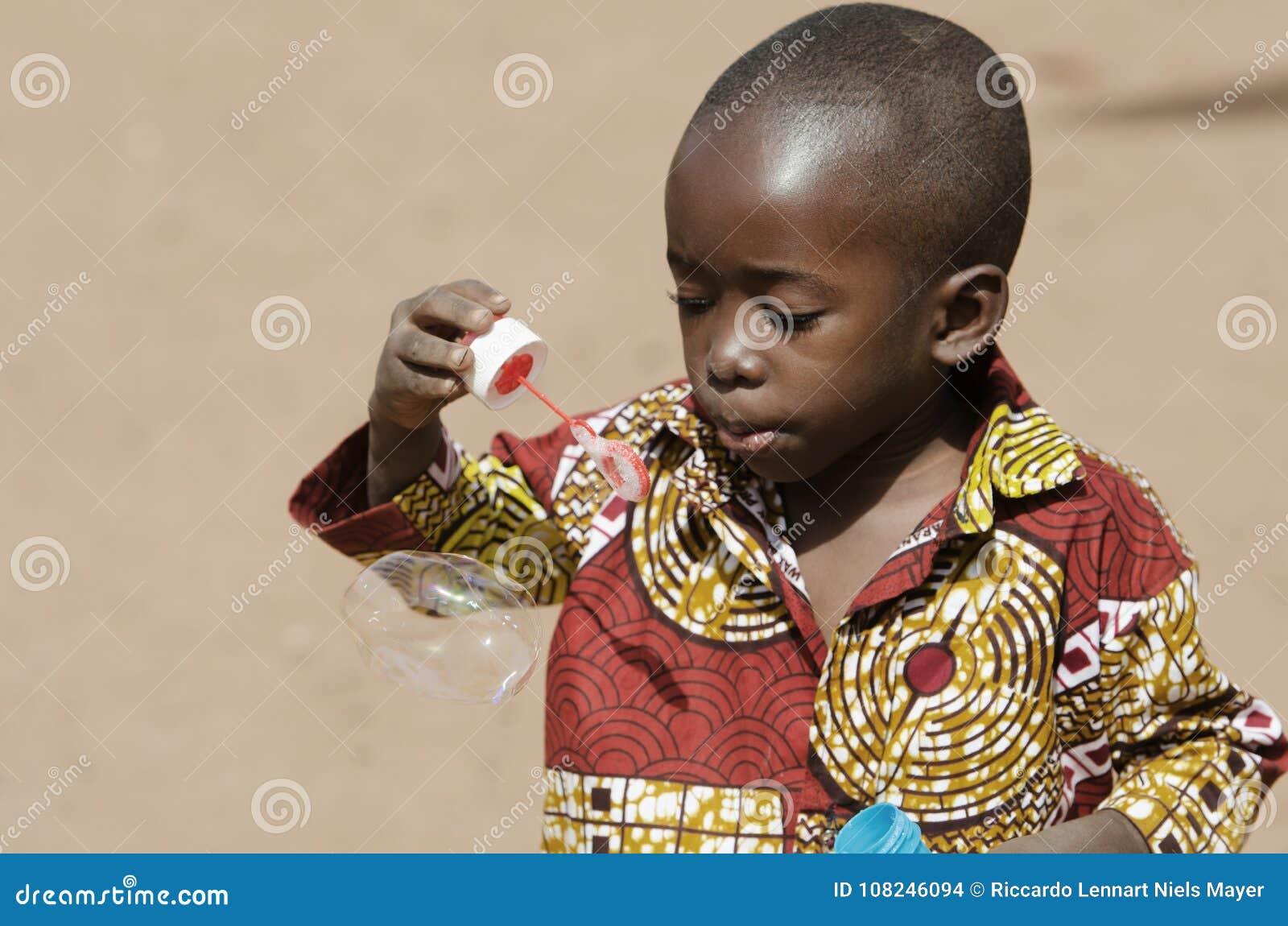 Bebê africano considerável que tem o divertimento fora com bolhas de sabão