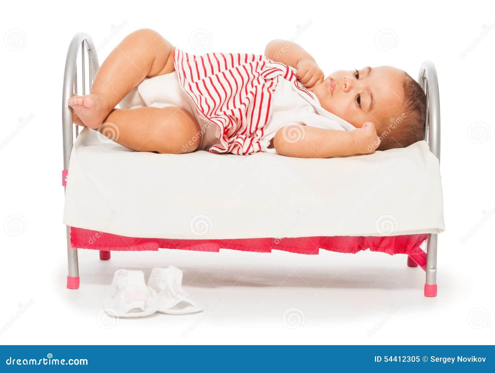 Bebê africano em vestido listrado na cama pequena