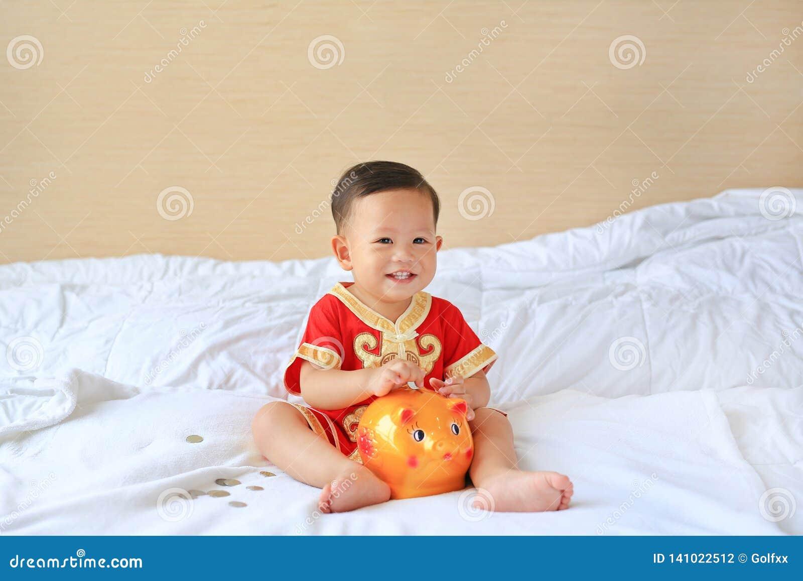 Bebê asiático pequeno feliz no vestido chinês tradicional que põe algumas moedas em um mealheiro que senta-se na cama em casa Eco