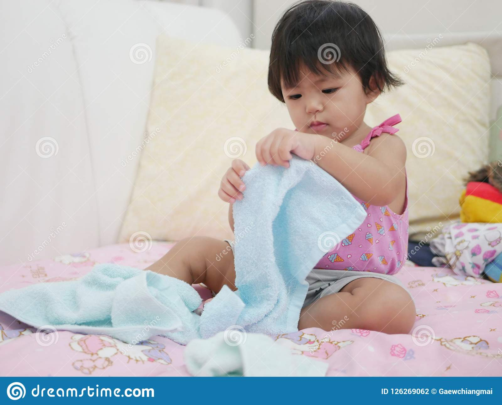 Bebê asiático pequeno que aprende dobrar a roupa