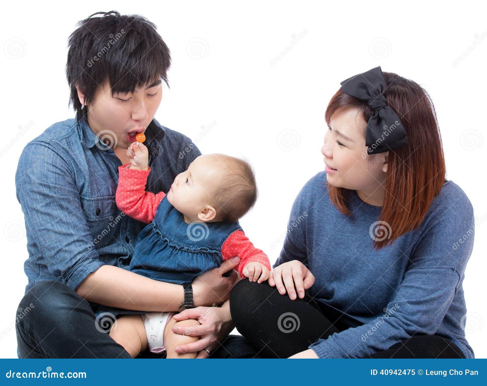 Bebê asiático que dá doces a seu paizinho