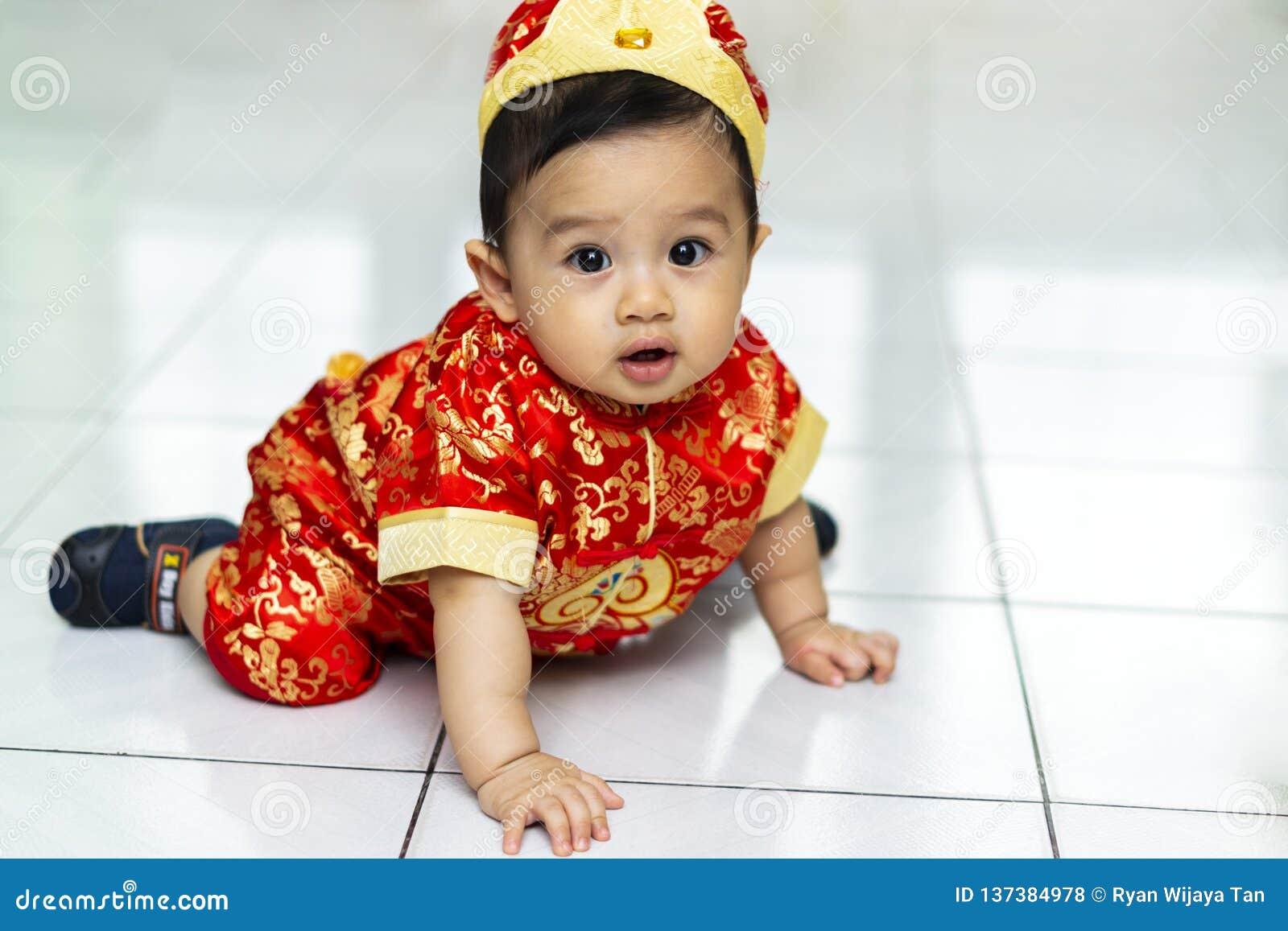 Bebê asiático que usa o vestido do cheongsam pelo ano novo chinês