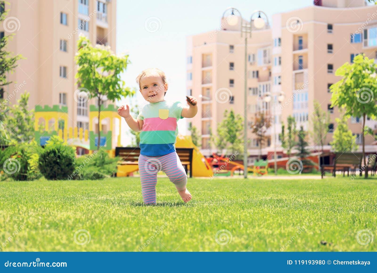 Bebê bonito que aprende andar fora