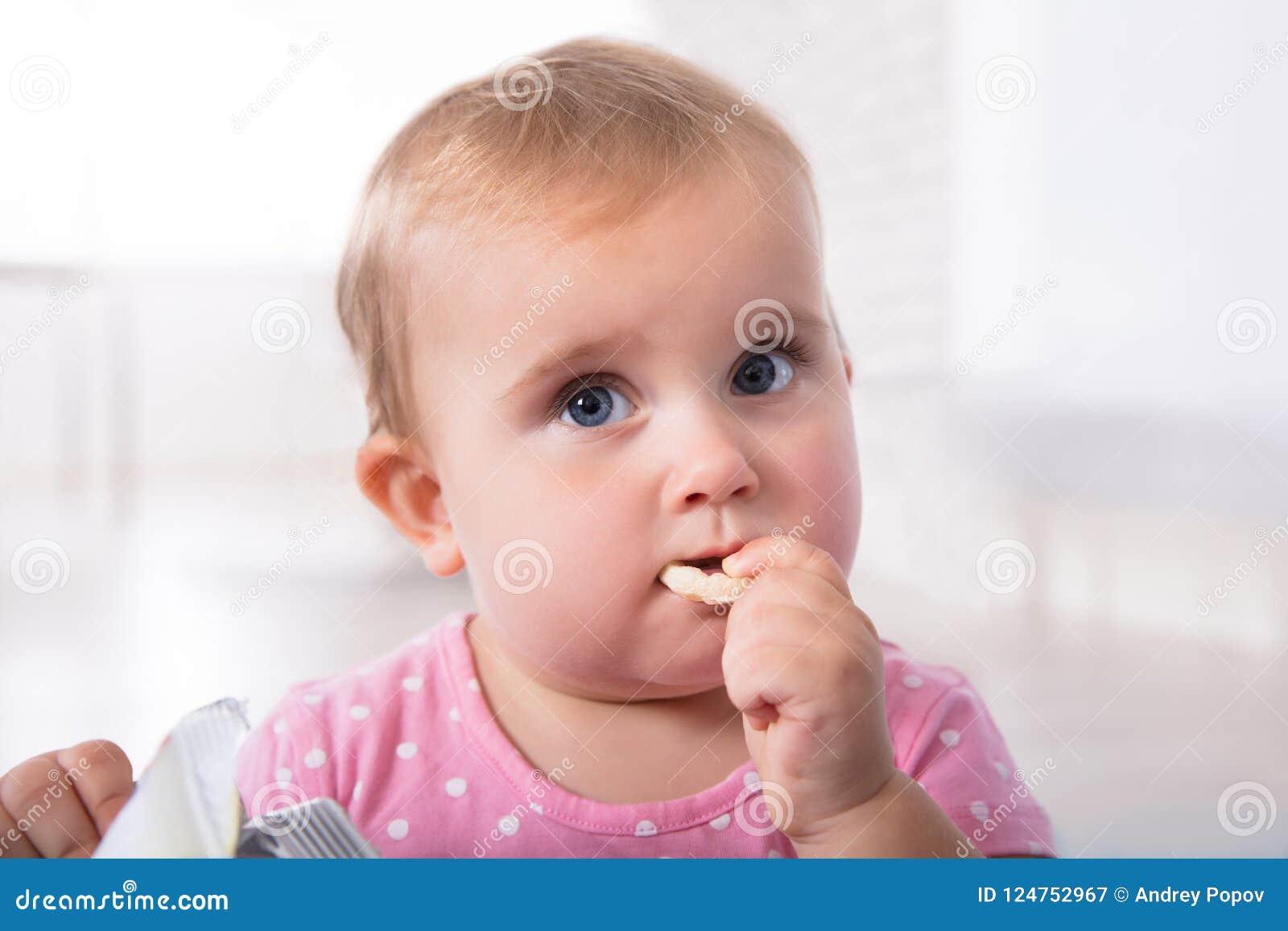Bebê bonito que come o alimento
