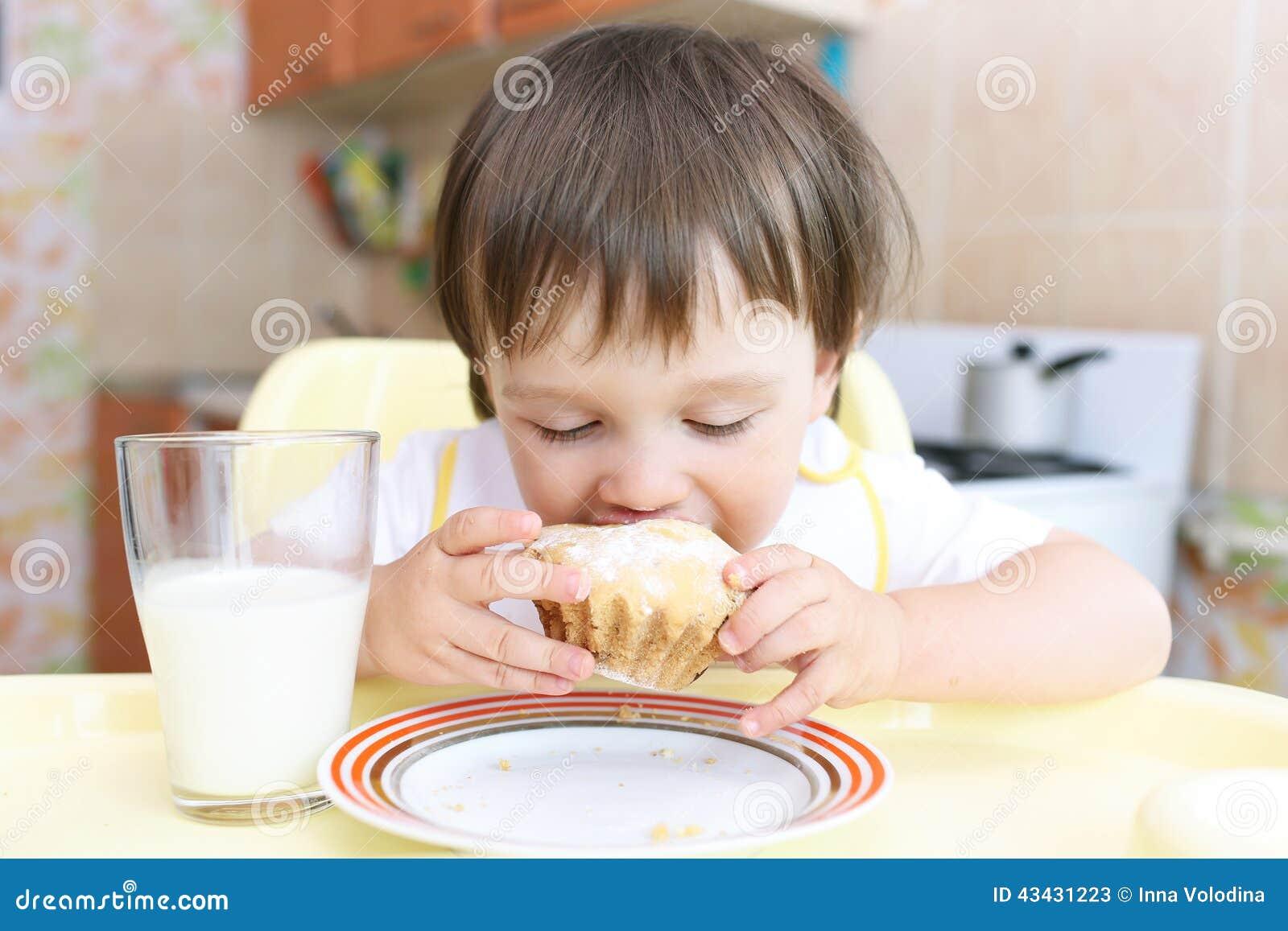 Bebê bonito que come o queque e o leite