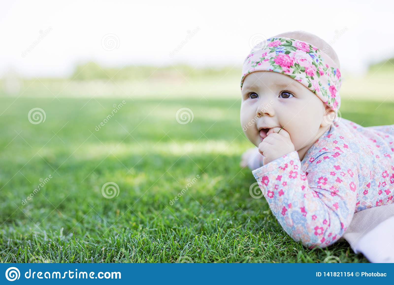 Bebê bonito que olha acima ao encontrar-se para baixo na grama no parque