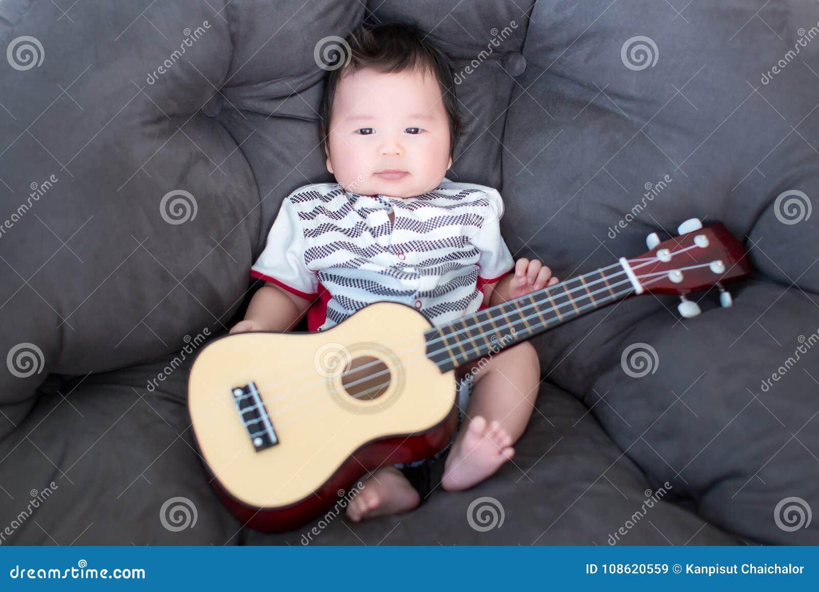 Bebê bonito que senta-se no sofá macio com mini guitarra músico dos bebês Habilidades da música da prática para crianças música e
