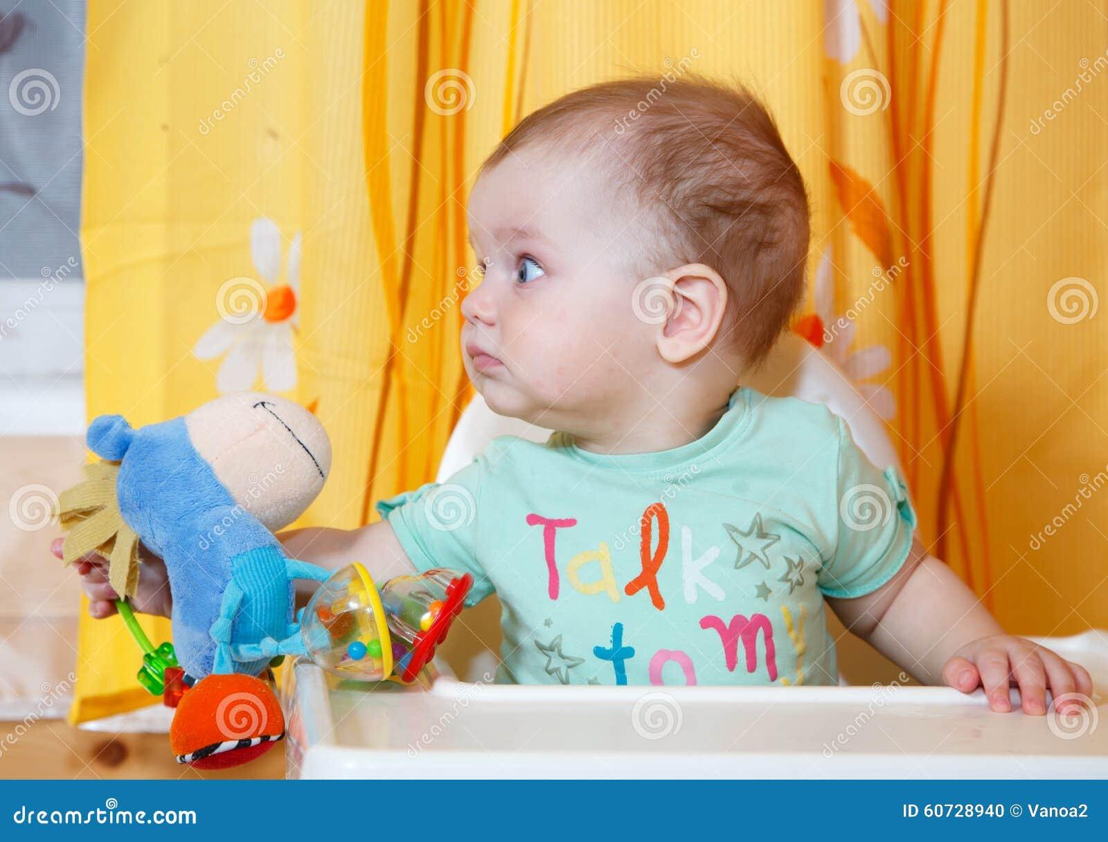 Bebê com fome com o brinquedo em seu alimento de espera da mão
