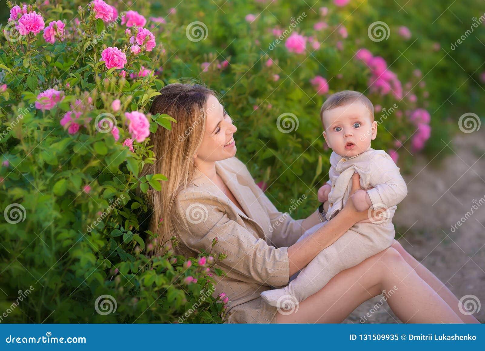 Bebê da terra arrendada da mulher no campo completamente de arbustos de rosas Estação de verão motherhood Tempo da família