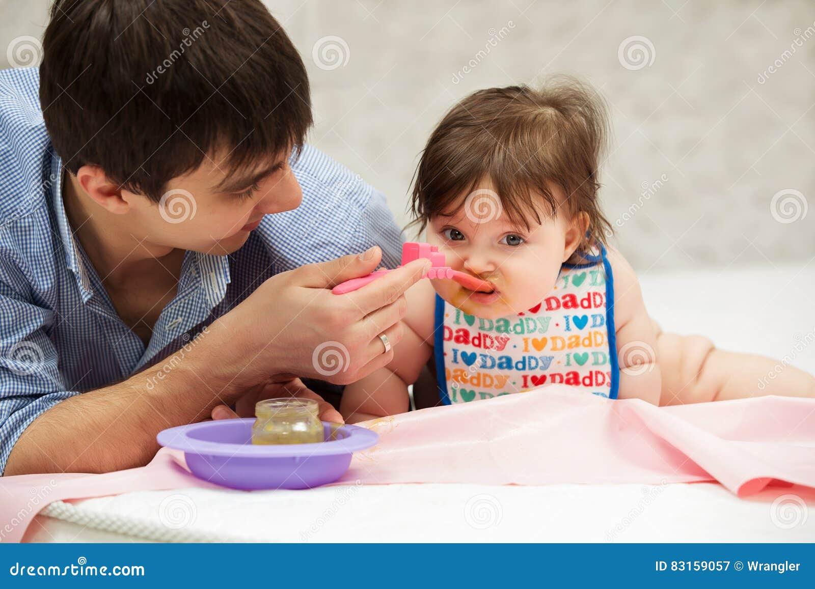 Bebê de alimentação do pai na cobertura em casa