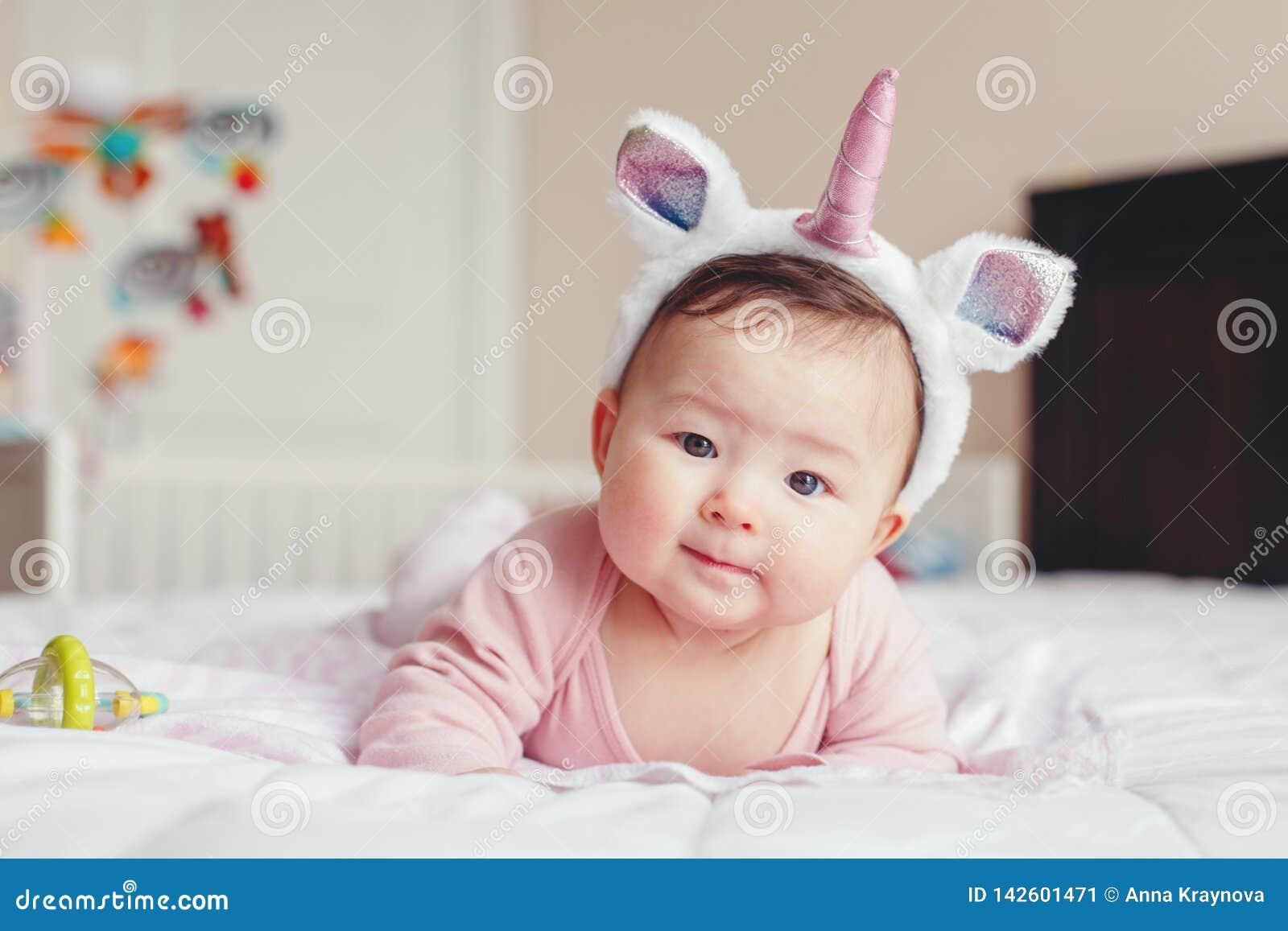 Bebê de sorriso asiático adorável bonito da raça misturada quatro meses de encontro velho na barriga na cama
