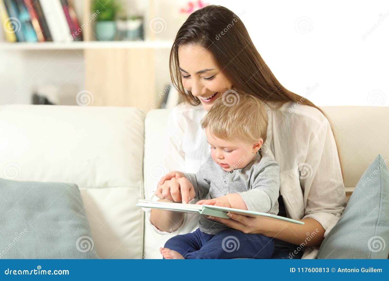 Bebê e mãe que leem um livro junto