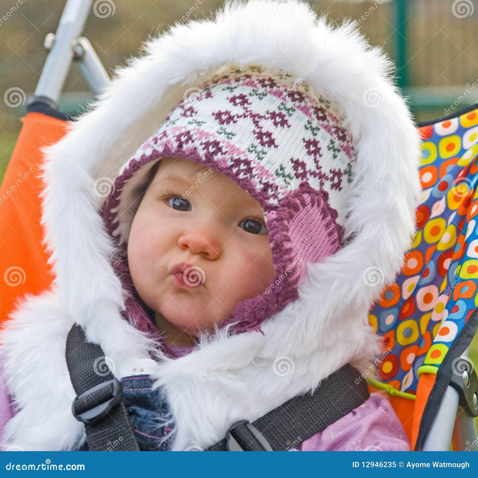 Bebê em um buggy com cintas da segurança.