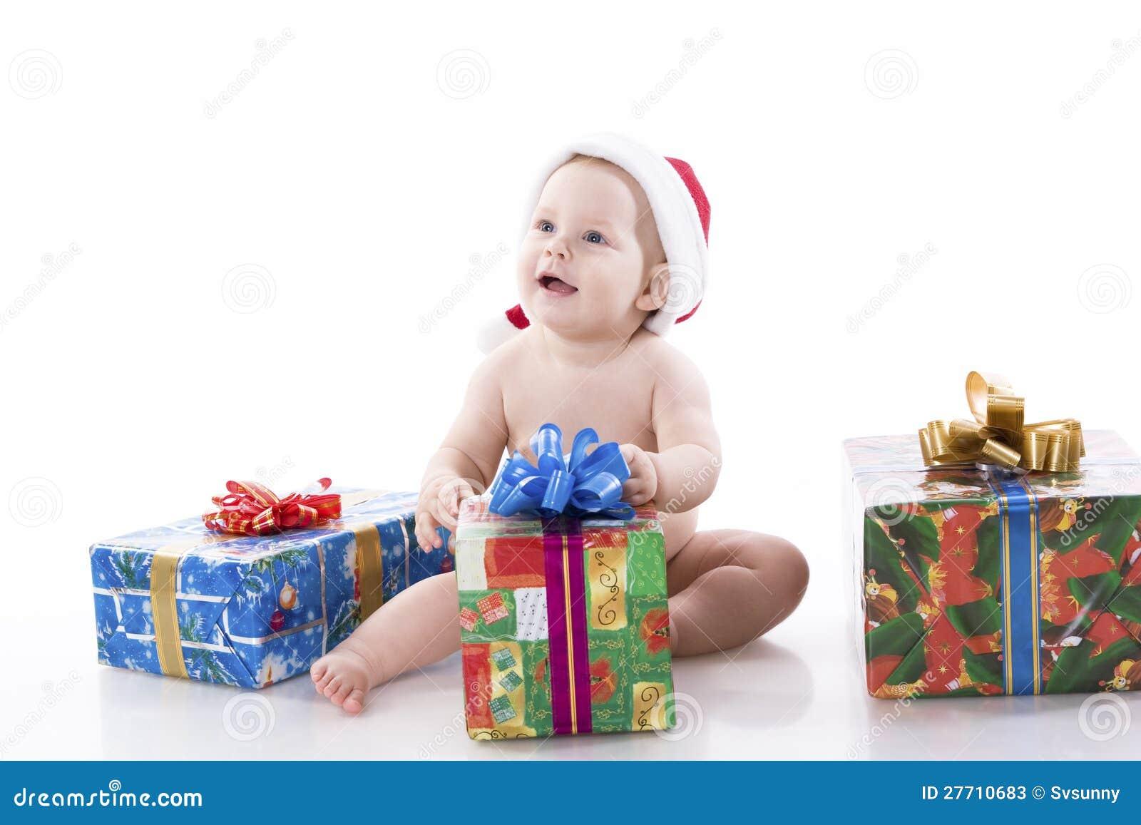 Bebê em um tampão de Papai Noel com presentes